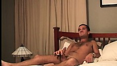 Hot Latino boy Luis sits fully naked on the bed pleasing his big shaft